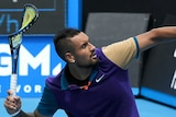 Tennis player Nick Kyrgios winds up to throw his broken racket off the court during a match.