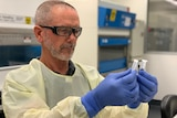 A man wearing a lab coat and goggles holding two test tubes