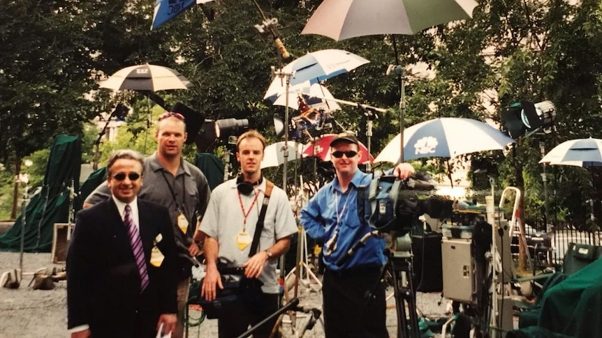 Cameraman standing next to camera and three other men with several large umbrellas around them.