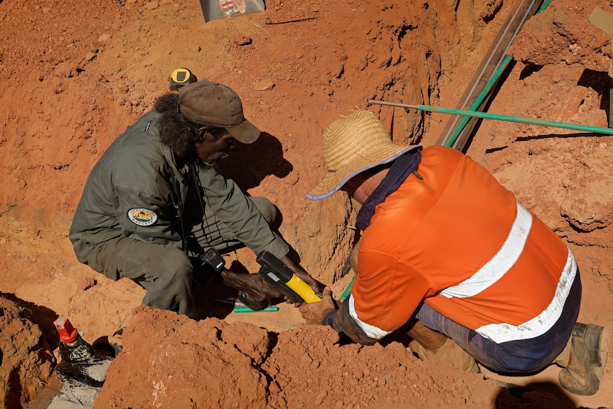 A ranger and a builder crouch down in the dirt to work on the construction of a crocodile farm.