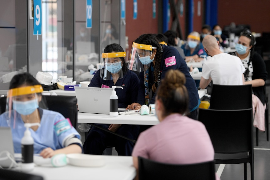 people in a room getting vaccinated by nurses in full PPE