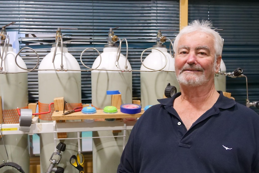 A man with white hair and a white beard faces the camera, with four gas cylinders in the background.