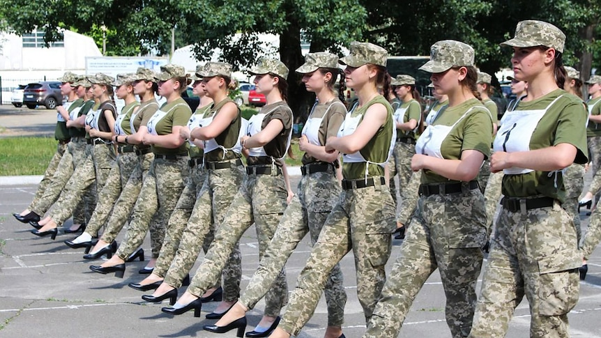 A group of women in army fatigues and high-heel shoes march together on a sunny day.