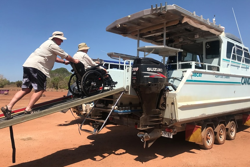 Man pushing father in wheelchair onto finishing boat.