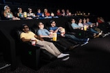 People sitting in reclining cinema seats watching a film.