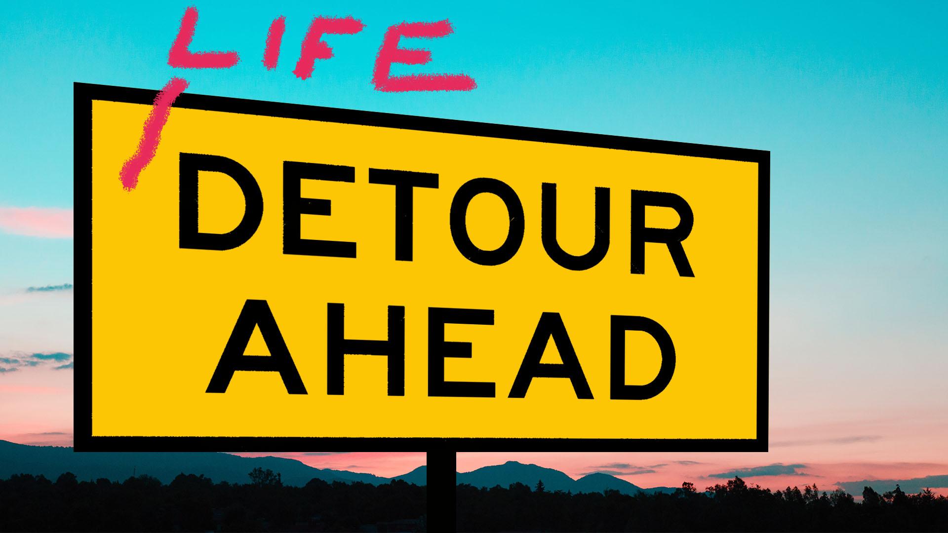 A 'detour ahead' road sign against a sunset horizon.