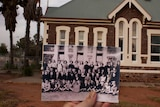 A black and white school class photo is held in front of an old brick building.