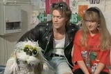Young man and woman sit close together framed for a TV show with a puppet dog.