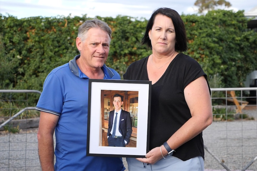 A father and mother hold a picture of their late son.