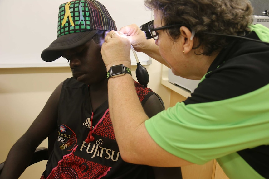 A health worker examining an ear of an Indigenous teenager using a tool.