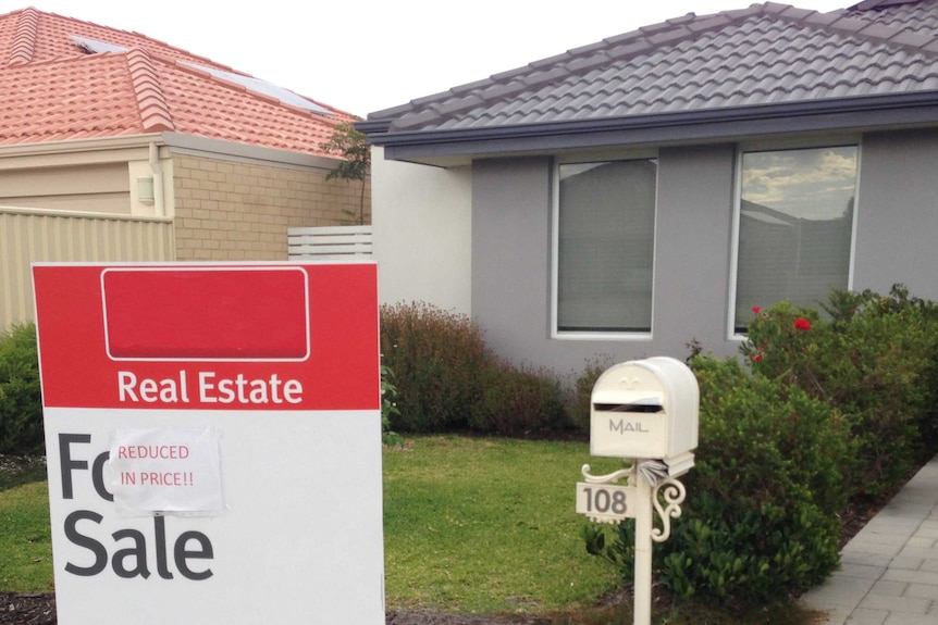 Sign saying price reduced on real estate for sale.