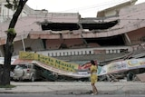 A woman walks in front of a collapsed shopping mall after an earthquake hit Padang