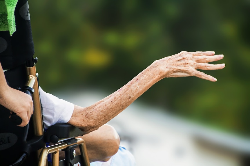 Stock image shows an elderly woman's arm sticking out from a wheelchair being pushed by a carer.