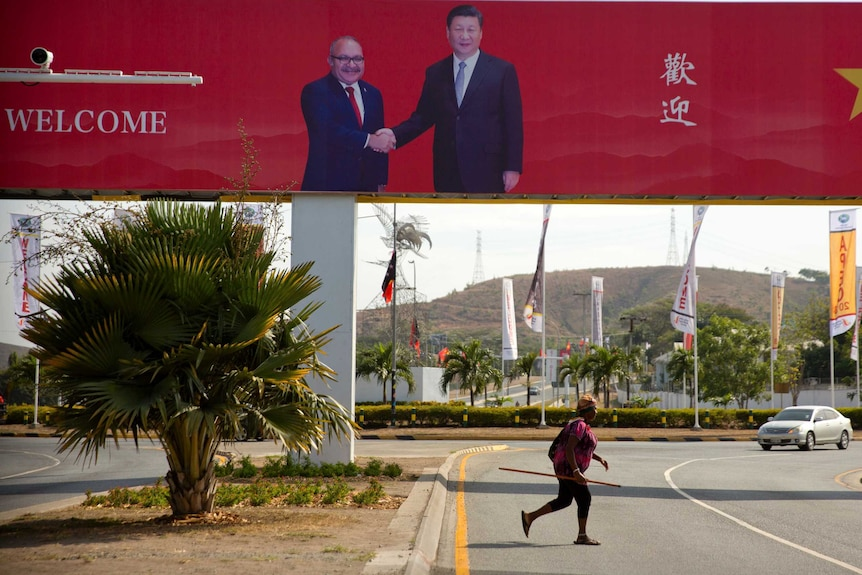 A woman crosses the street near a billboard commemorating the state visit of Chinese President Xi Jinping in Port Moresby.