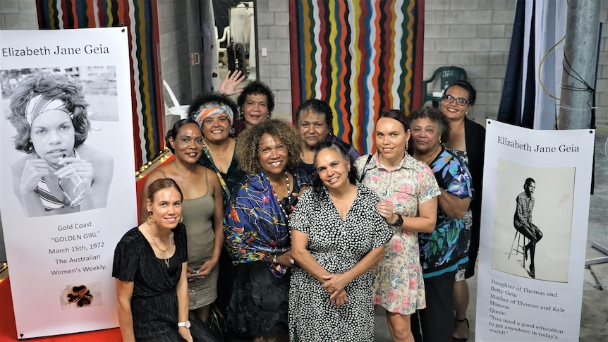 Ten women stand together in front of banners of Elizabeth Geia at fashion show event