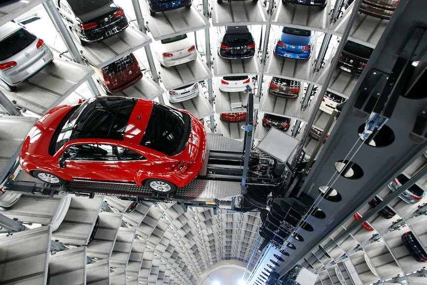 A large car tower carries a multitude of vehicles parked in their respective slots, with a red VW Beetle lifted into a spot.
