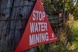 a red sign reading 'stop water mining' is nailed to an old wooden fencepost.