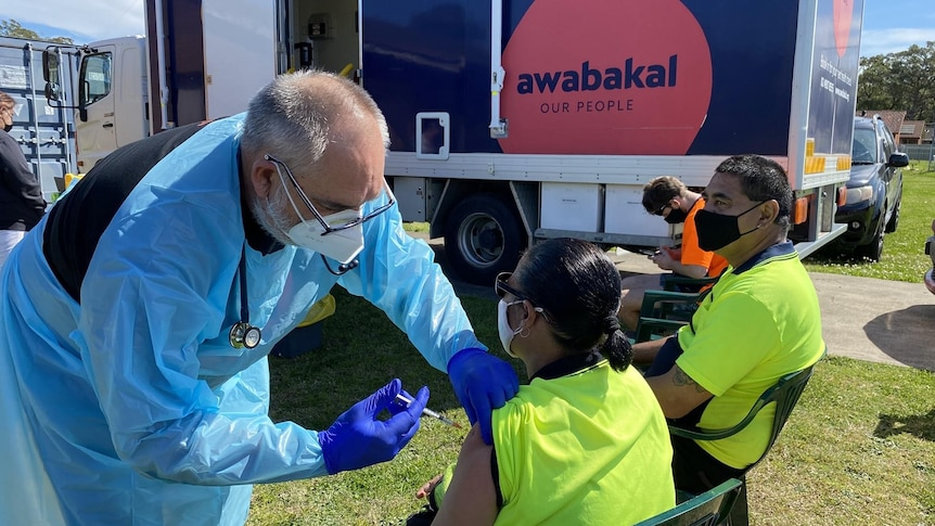 A man in protective gear injects a vaccine into the arm of an Aboriginal woman.