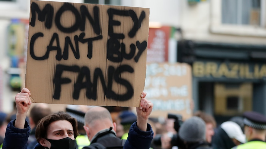 """A young male holds up a sign that reaeds """"MONEY CAN'T BUY FANS""""."""