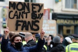 "A young male holds up a sign that reaeds ""MONEY CAN'T BUY FANS""."