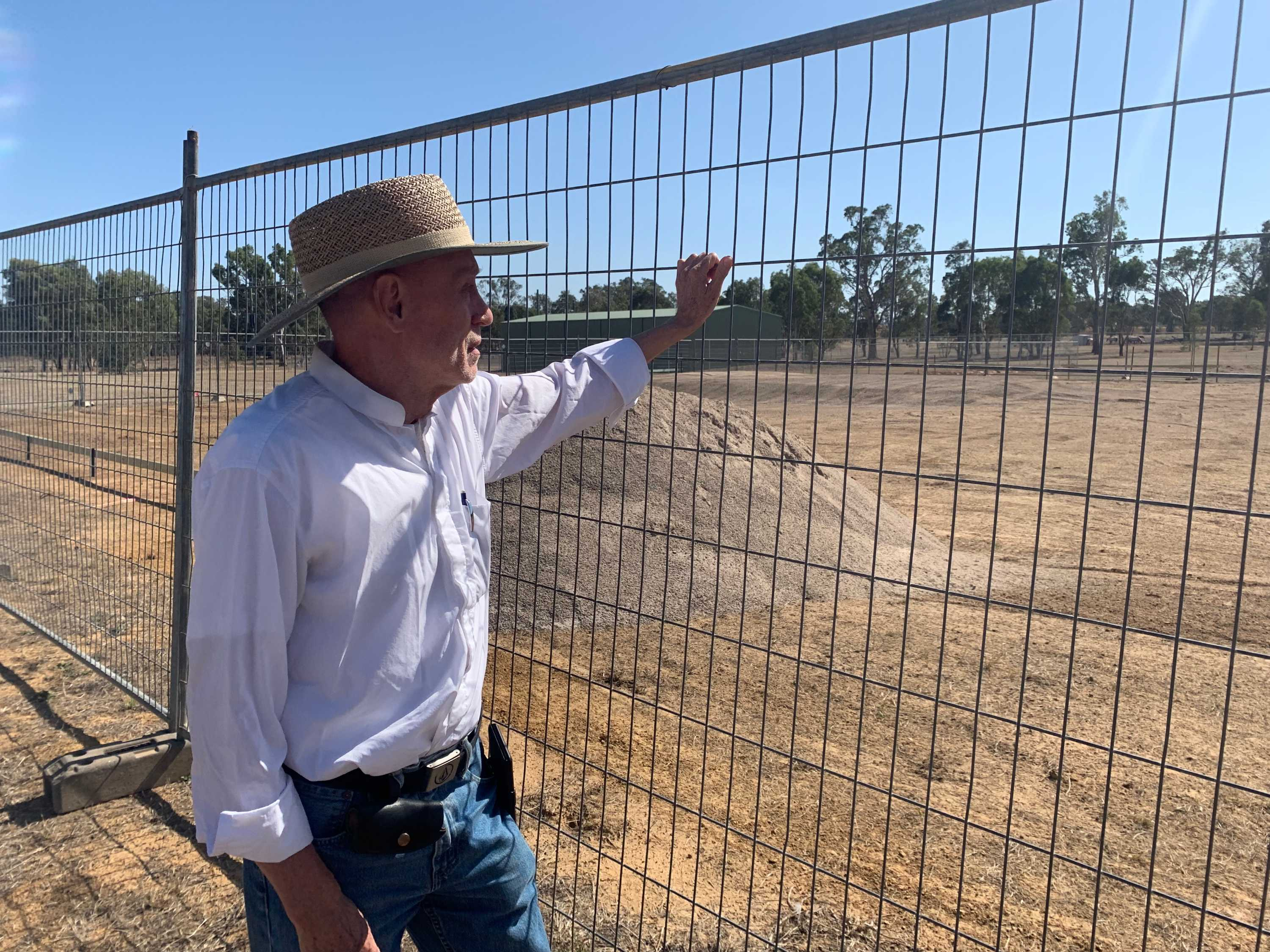 Man in hat leans against a fence
