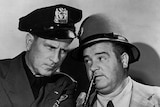 Bud Abbott and Lou Costello are dressed in police hats as they pose for a publicity photograph.