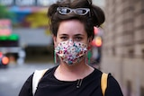 A woman is walking down a street wearing a colourful face mask.