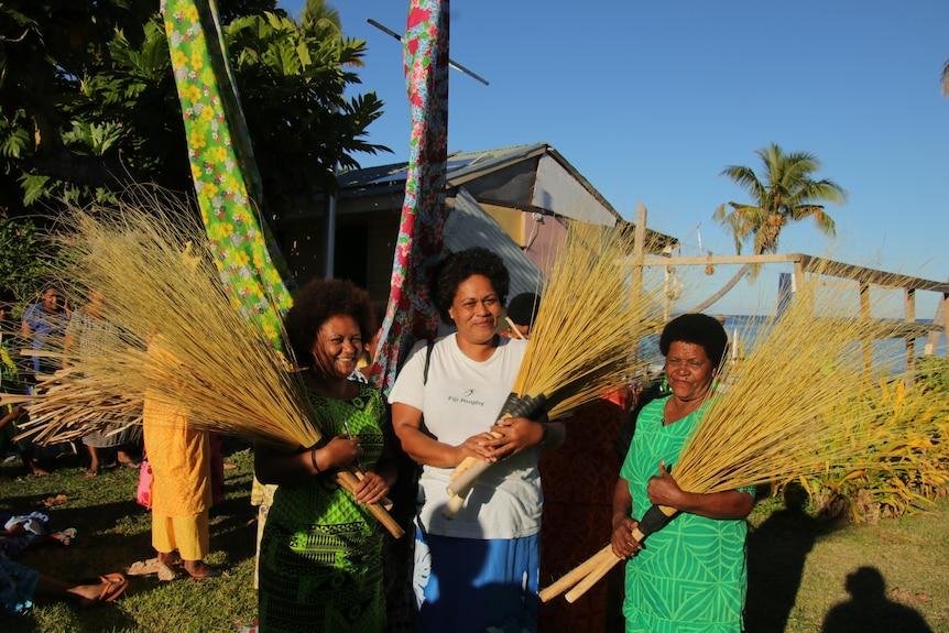 Three women holding pandanus leaves