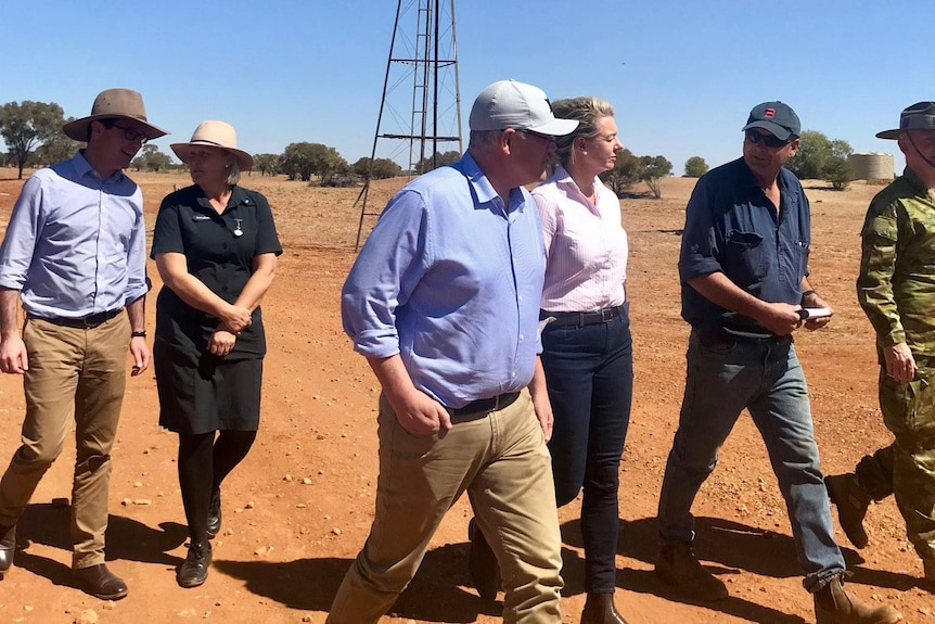 Scott Morrison in a cap, shirt with sleeves rolled up, chinos and boots, walks among a crowd on red dirt in front of a windmill.