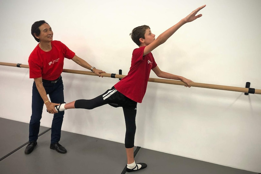 Ballet student Presley Tanner holds on to a barre while dancer Li Cunxin adjusts the position of Presley's leg.