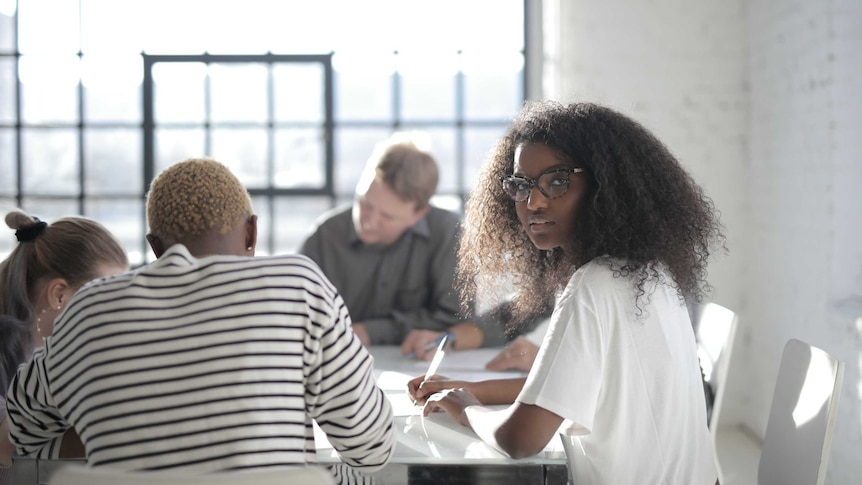 Woman looks at camera while colleagues work at table to depict talking about pay/salary to close gender and racial pay gaps.