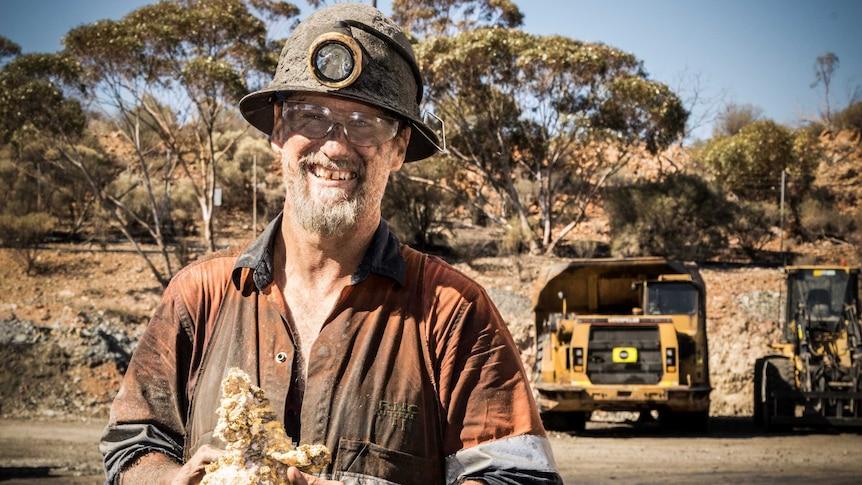 Miner holding gold specimen