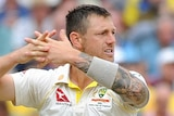 Australia bowler James Pattinson interlocks his fingers and looks away to the side.