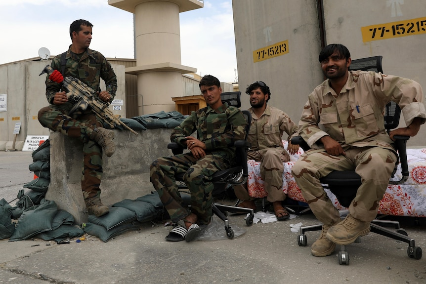 Afghan security forces sit at Bagram air base, one holding a weapon.