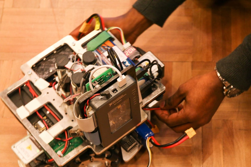 Close up of a robot with wires coming out of it as two hands plug red wires in