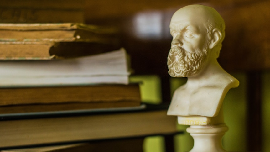 An alabaster bust of Socrates sits next to a pile of books.
