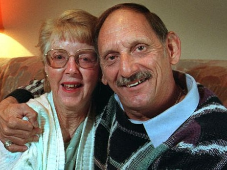 A heterosexual couple in their seventies, a blonde woman with glasses and a man wearing a patterned jumper, embrace and smile.