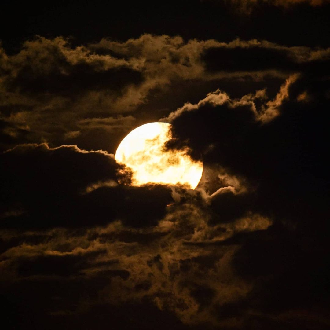 A bright glowing moon behind dark clouds at night time.
