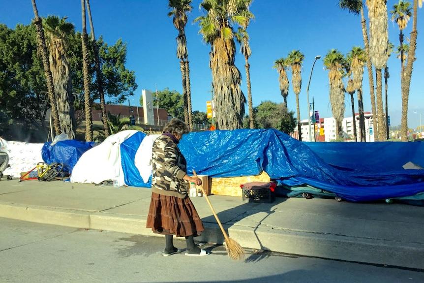 Women sweeps outside an LA tent encampment