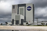 White building with NASA logo on it, dark grey rain clouds in the background.
