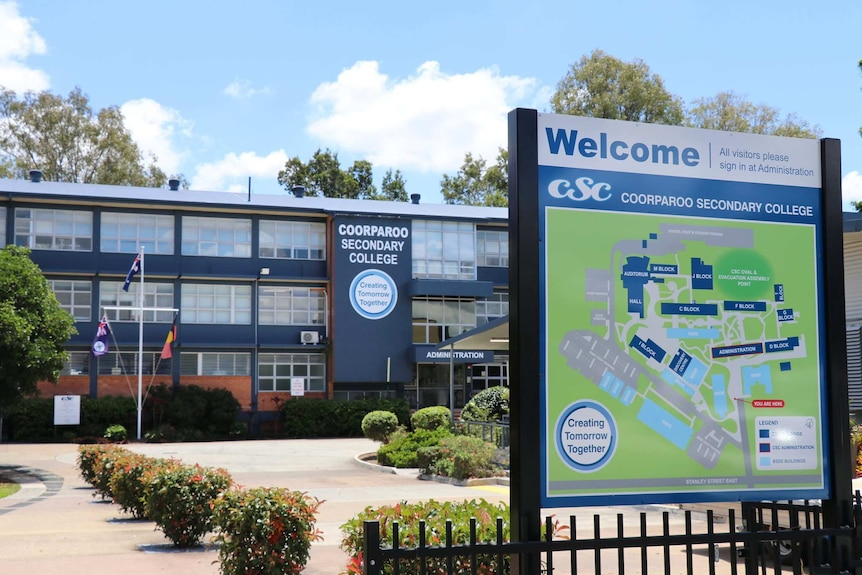 An image showing the entrance to Coorparoo Secondary College, with a school sign and map in front of gardens and navy building