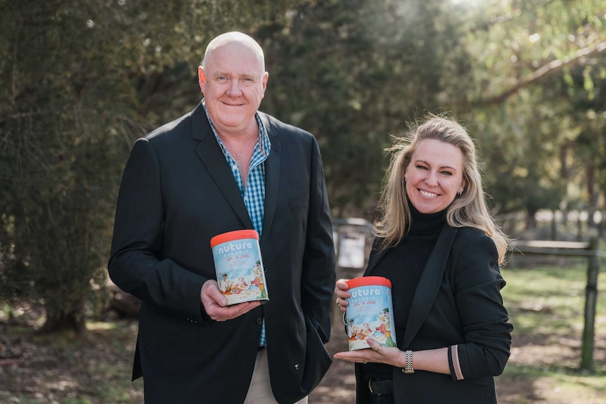 A man and a woman hold two cans of infant formula in a garden