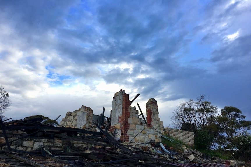 A house ruins sit beneath a stormy sky
