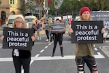 Protesters holding signs reading 'this is a peaceful protest' block Flinders Street.