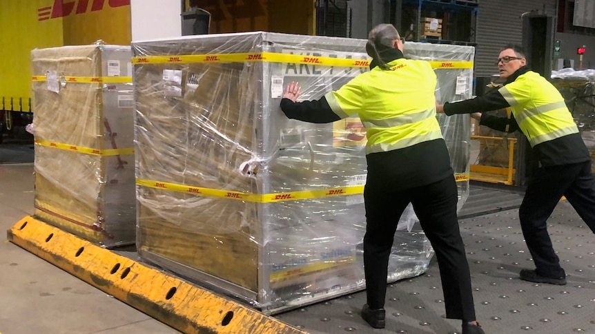 Two workers in hi vis at an airport, pushing a crate wrapped in plastic into a truck.