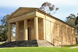 A sandstone building with columns in a Australian bush setting
