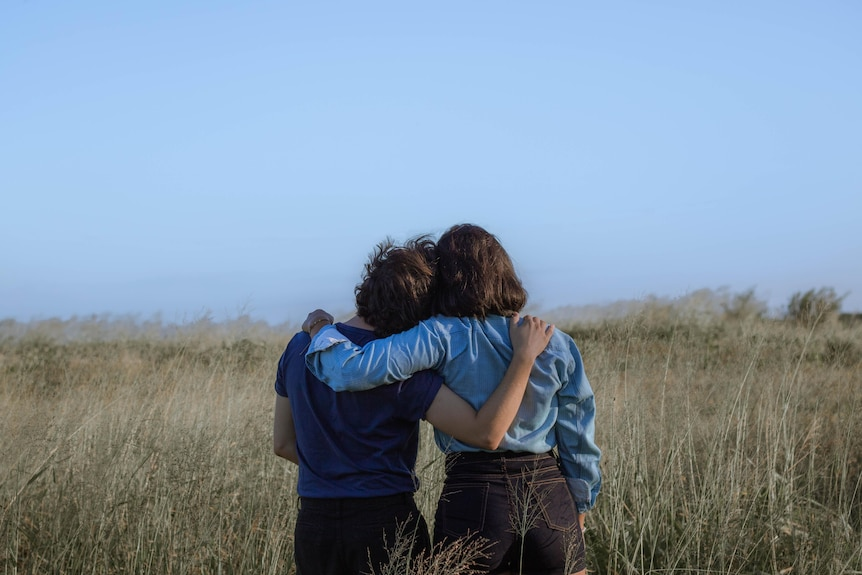 Two women, with their backs to the camera have their arms around each other showing support.