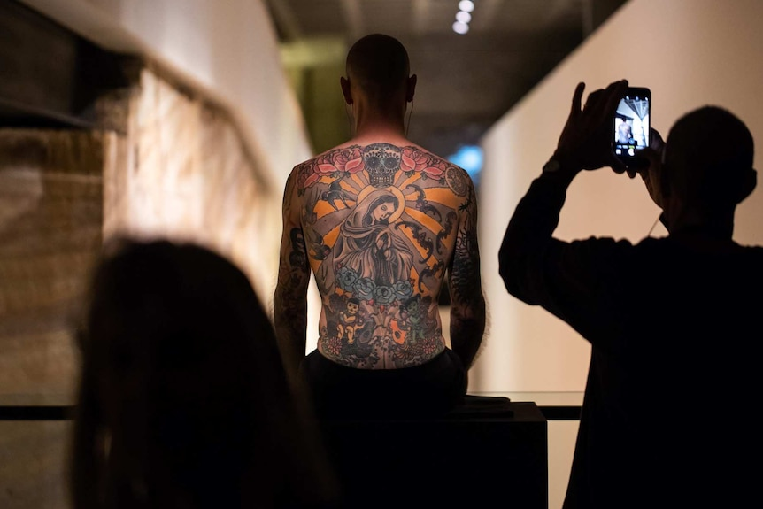 Tim, the tattooed man, sits as part of the artworks at MONA, Berriedale, Hobart.