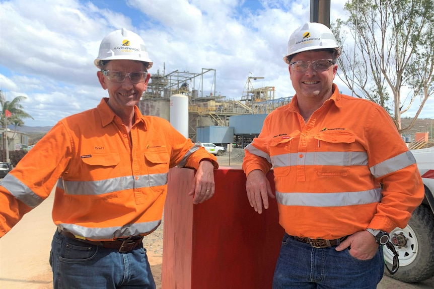 Two men in hi vis shirt and hard hats stand in front of structures at a mining site.