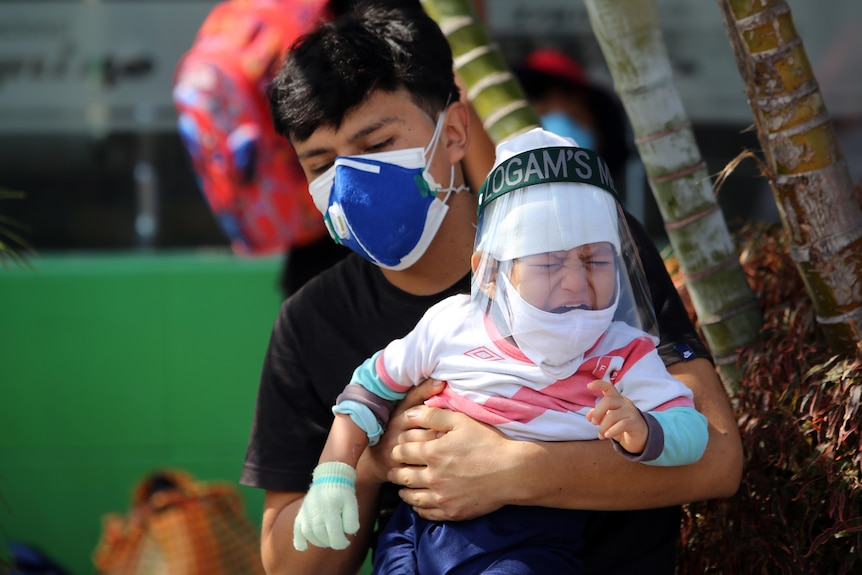 Peruvian man with crying baby